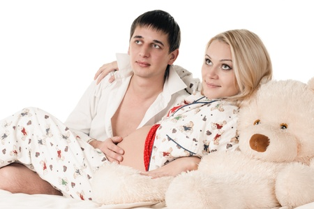 young happy man and pregnant woman lying on bed photo