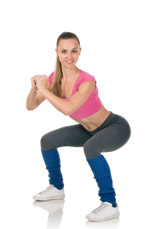 young happy woman does fitness exercise on white background. Smiling and very slim. Whole length. Stock Photo - 17252682