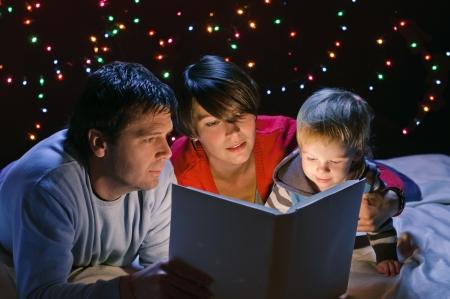 pareja en la cama: joven familia feliz con el libro en la guirnalda de luz de fondo