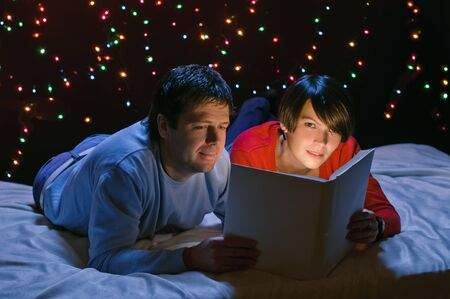 young happy couple with light book on garland background photo