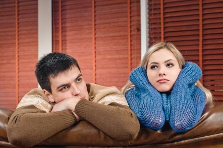 mujeres tristes: joven pareja en el sof� en el apartamento