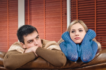 bored woman: young couple on the sofa at the apartment Stock Photo