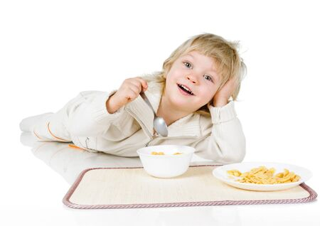 little boy with plates of yellow cereals on white photo
