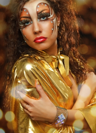 young beauty girl with art make up in gold mant on light background photo