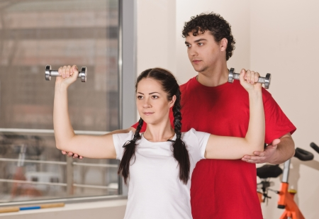 instructs: young man instructs woman with dumbbells in fitness club