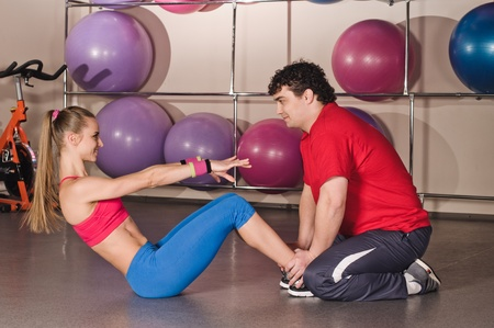 instructs: young man instructs woman in the fitness club Stock Photo