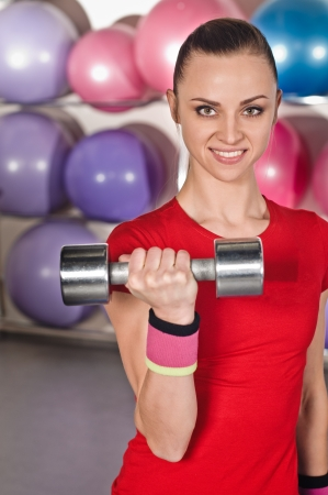 only the biceps: portrait of young woman with dumbbell on ball background