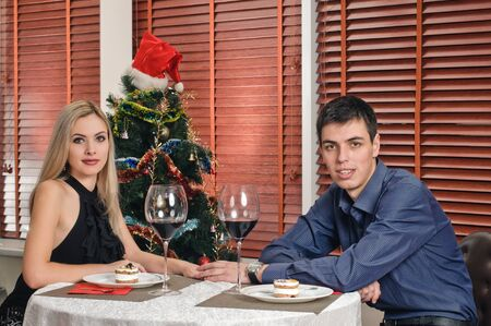 portrait of young couple about new year tree with glasses of wine photo
