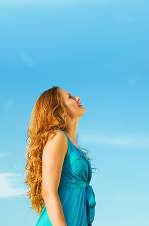young beautiful woman on the blue sky background photo