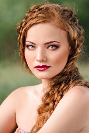 portrait red haired young woman with plait in summer photo