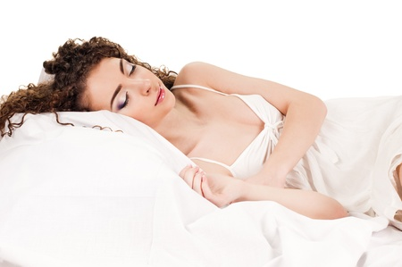 young woman sleeps on the white bed photo