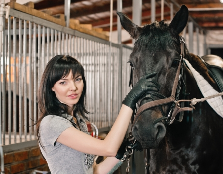 portrait of young woman with horse in the barn 写真素材