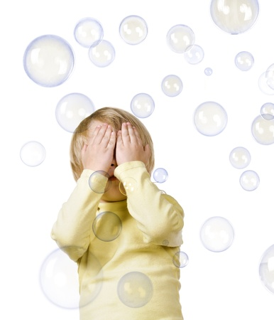 closes eyes: little boy closes eyes from bubbles on white background Stock Photo