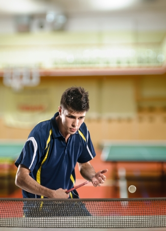 young man table tennis-player in play on sport club background photo