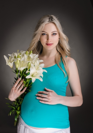 young pregnant woman with flowers on dark background photo