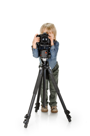 little boy with camera on tripod full length on white background photo