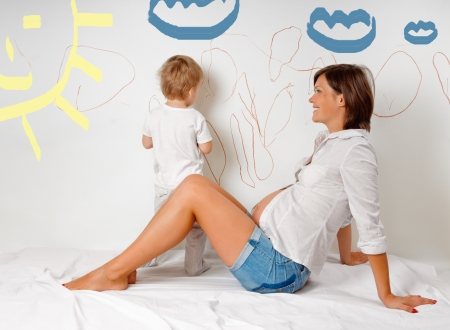 young pregnant mother with her son on white bed about the wall photo