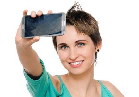 Smiling woman taking a selfie using her smartphone. isolated on white photo