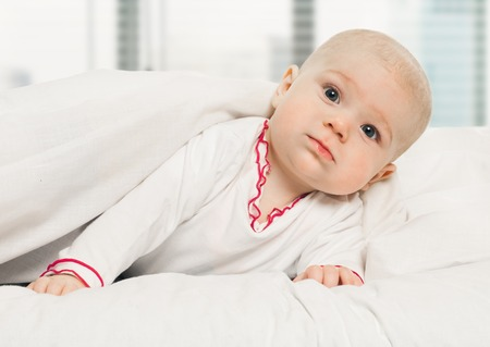Adorable baby, looking out under a white blanket, cover. on window background photo