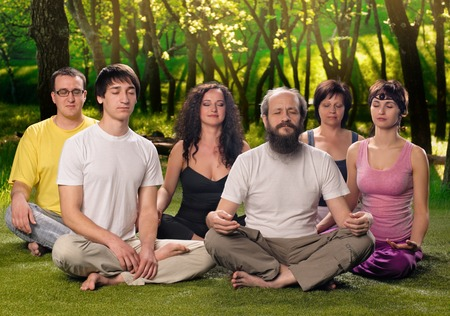 A group of people doing yoga together or meditation outdoors Stockfoto