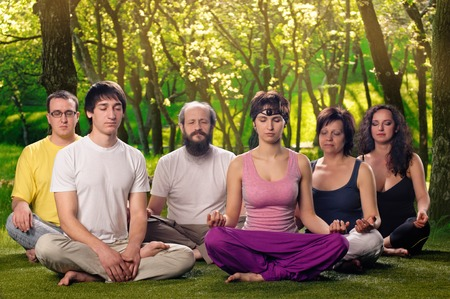 A group of people doing yoga together or meditation outdoors 写真素材