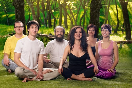 therapy group: A group of people doing yoga together or meditation outdoors Stock Photo