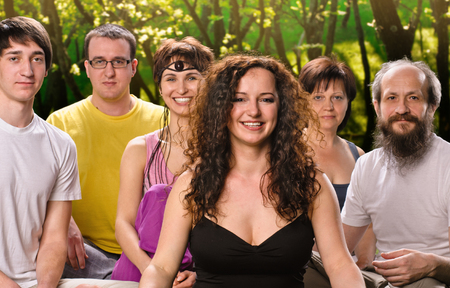 portrait young woman in yoga meditation class with group of people outdoors photo