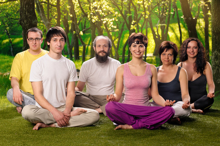 A group of people doing yoga together or meditation outdoors photo