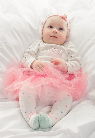 a young baby: A young baby on a white bed in pink dress Stock Photo