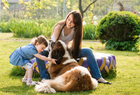 mother and child playing with dog on nature. outdoor about sander photo