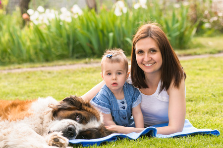 mother and child playing with dog on nature. outdoor photo