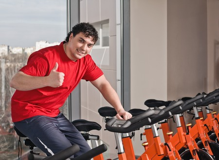 Portrait of young man on spinning bike in health club. Thumbs up. photo