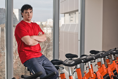 Portrait of young man on spinning bike in health club. photo