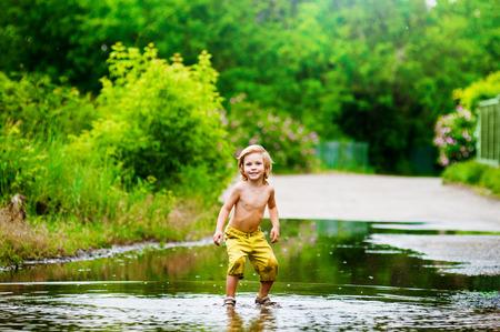 Little boy runs through a puddle. summer outdoor photo