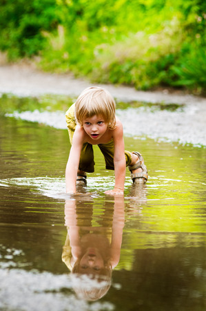 little happy boy in the puddle. summer outdoor photo