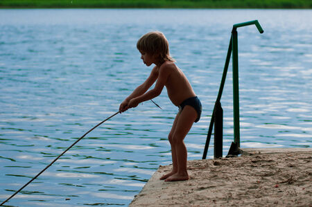 Boy fishing on the bank of small river photo