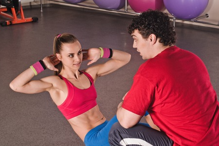 Woman training abdominal on the floor in the gym with a personal trainer photo