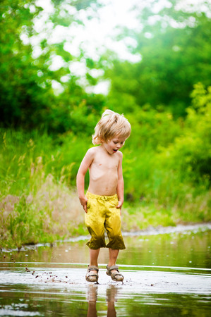 little happy boy jumping in puddle. summer outdoor photo