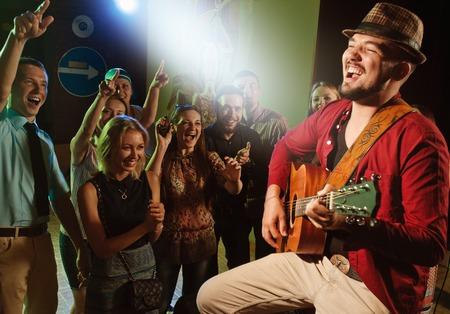 zábava: zpěvák a kytarista předvádění na jevišti v klubu před jásající dav