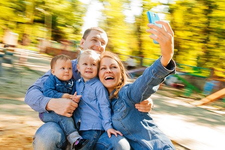 Family having fun on spinning roundabout. selfie Portrait. Naturally blur motion photo