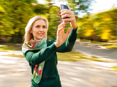 young beautiful woman taking selfie outdoor on the carousel photo