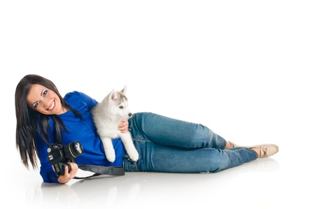 playing woman with puppies of siberian haski on white background photo