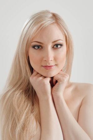 cabello rubio: Retrato de la hermosa mujer rubia joven con la cara limpia. en gris