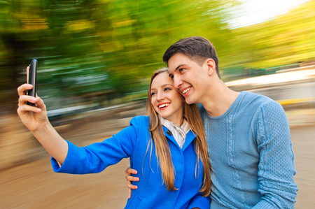 Beautiful young couple taking photos with mobile photo