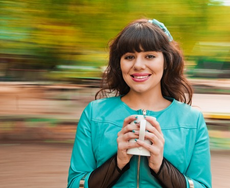 Attractive woman with a cup. background with natural motion blur photo