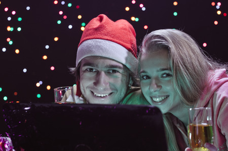 Online Shopping. Happy Smiling Young couple with Laptop. Christmas and New Year Gifts. photo