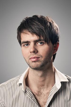 modelos hombres: Retrato de un joven serio smart pie contra el fondo gris
