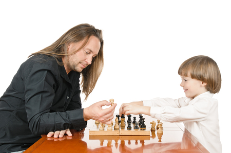 Father teaching his son playing chess. on white background photo