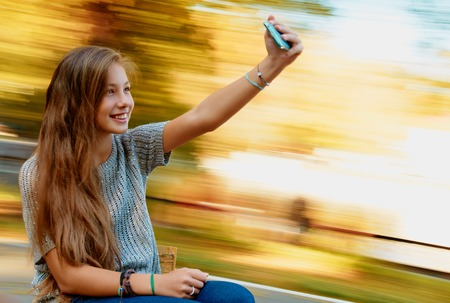 young beautiful girl taking selfie outdoor on the carousel photo