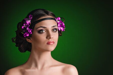 Beauty portrait of young woman with purple floral wreath over dark green background photo